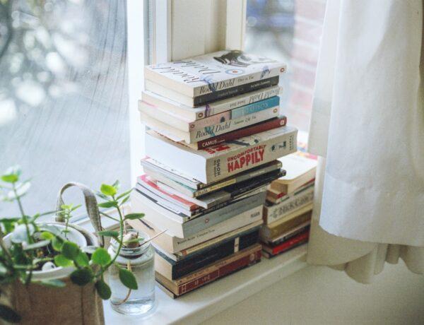 una pila di libri accanto alla finestra