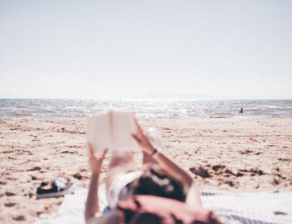 una ragazza che legge sulla spiaggia