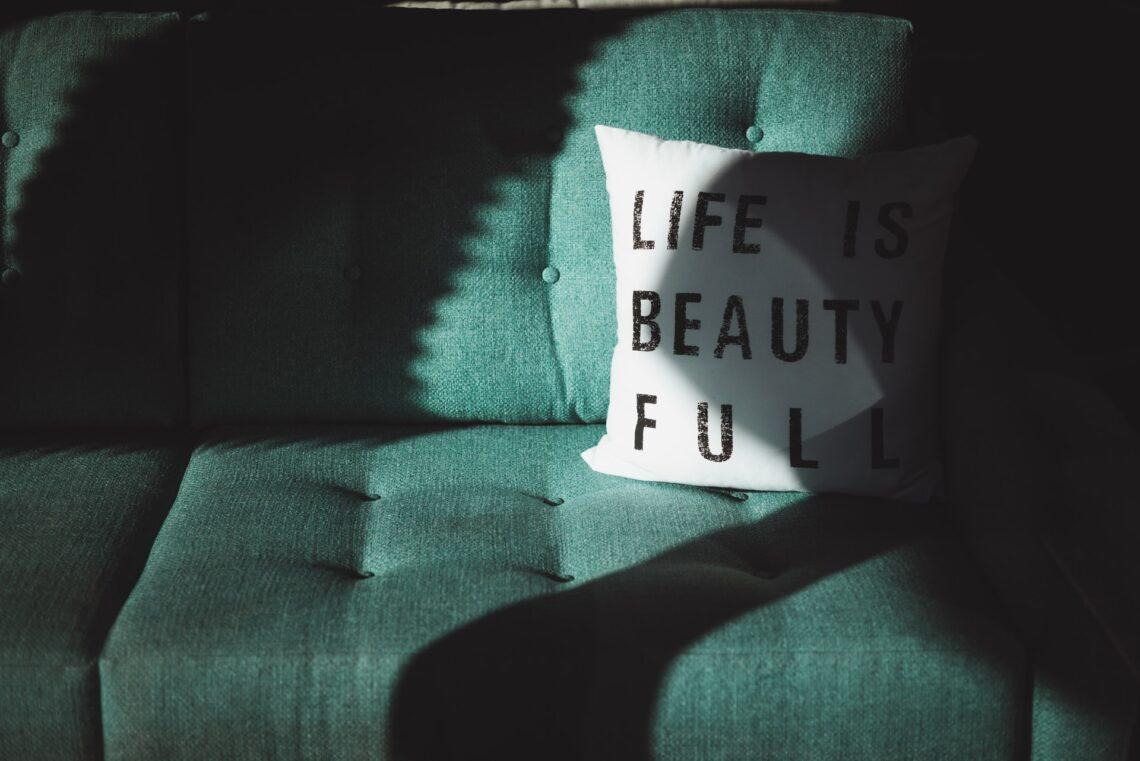 un divano verde e un cuscino in bianco e nero