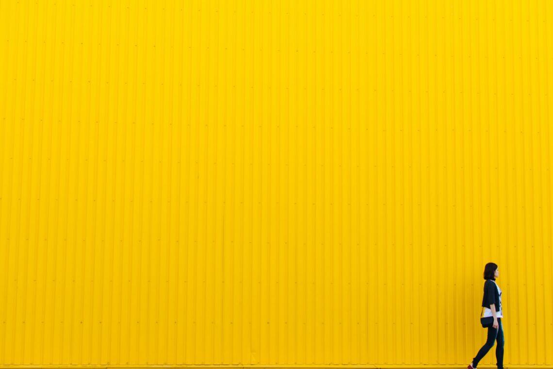 una donna cammina lungo una parete gialla