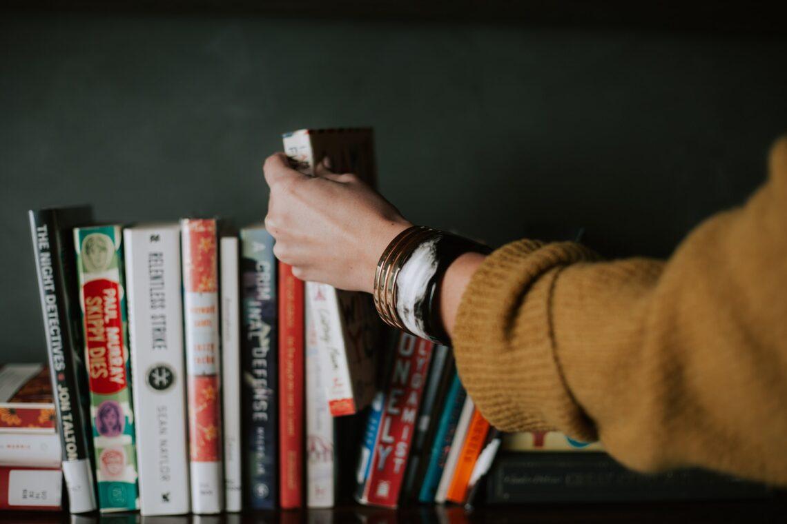 una ragazza sceglie un libro da leggere