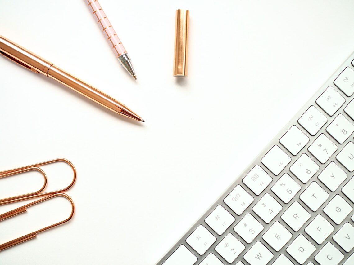 una scrivania con penne e tastiera
