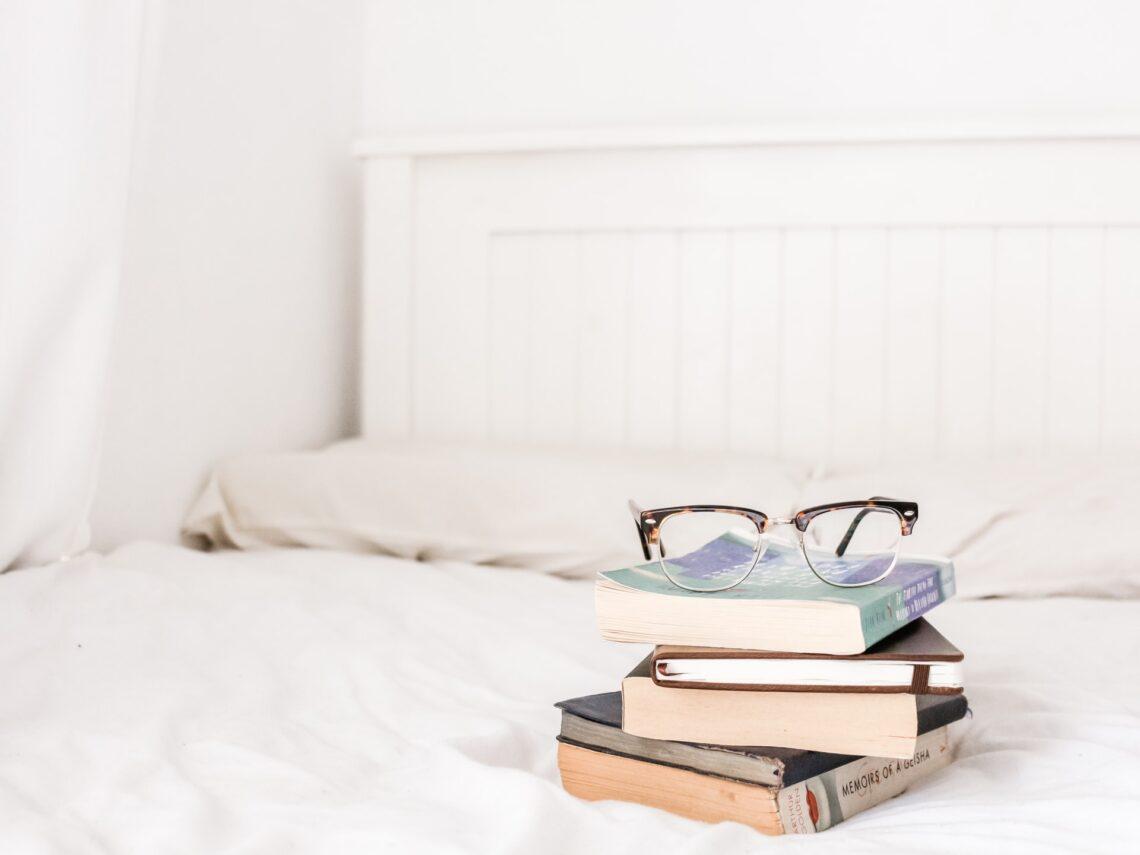 una pila di libri sul letto