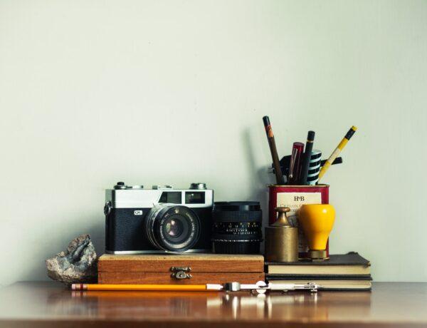 una scrivania con una macchina fotografica, timbri e un portapenne