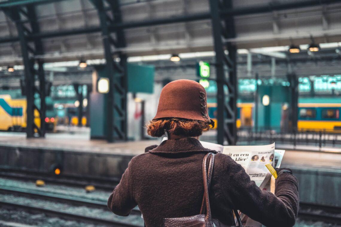 una donna di spalle legge il giornale alla stazione