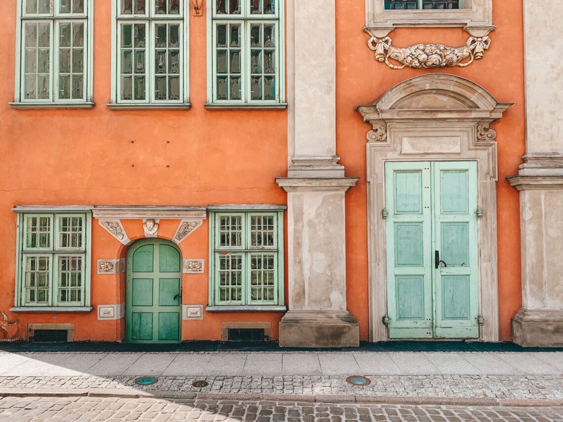 un palazzo con la facciata arancione e le finestre menta