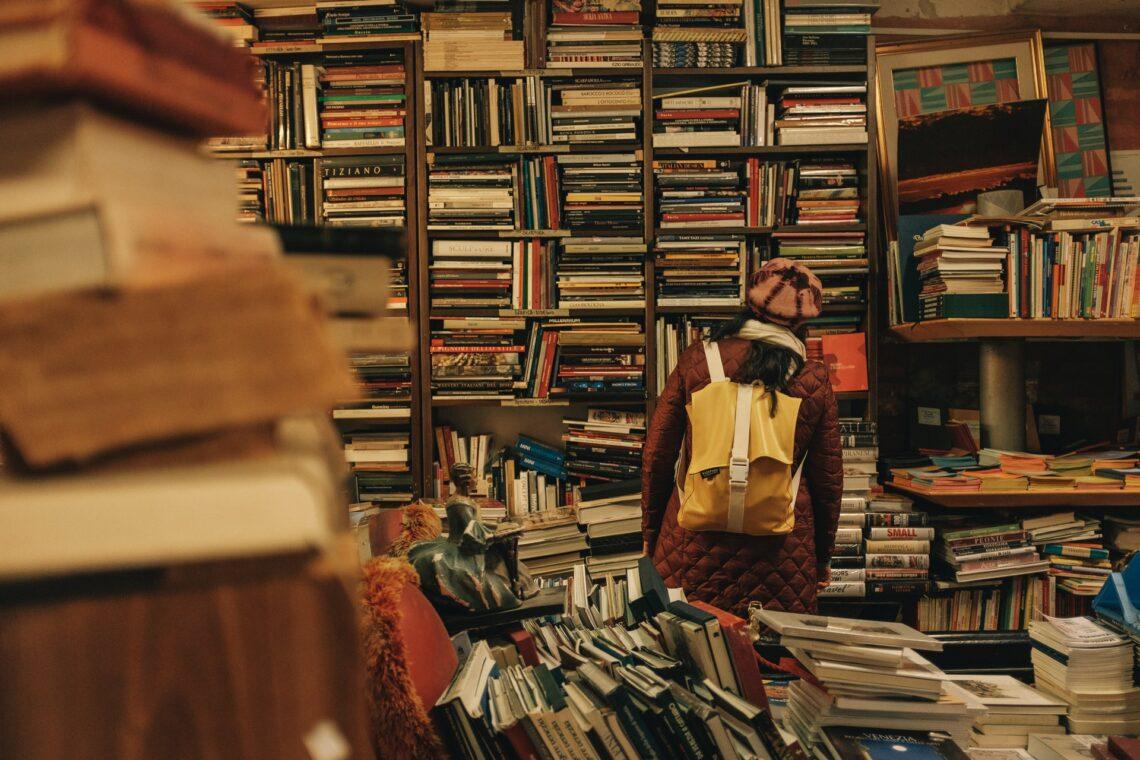 una ragazza con uno zaino davanti a uno scaffale pieno di libri