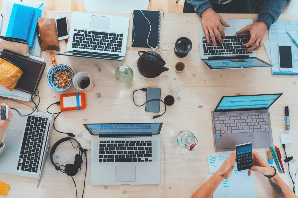 una scrivania con tanti pc portatili e persone che lavorano tra tazze di caffè e snack
