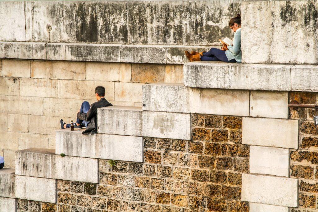 una donna legge un libro su una scalinata; più in asso un uomo è seduto con accanto una bottiglia di birra