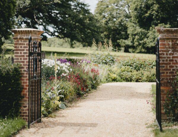 un cancello che si apre su un giardino fiorito