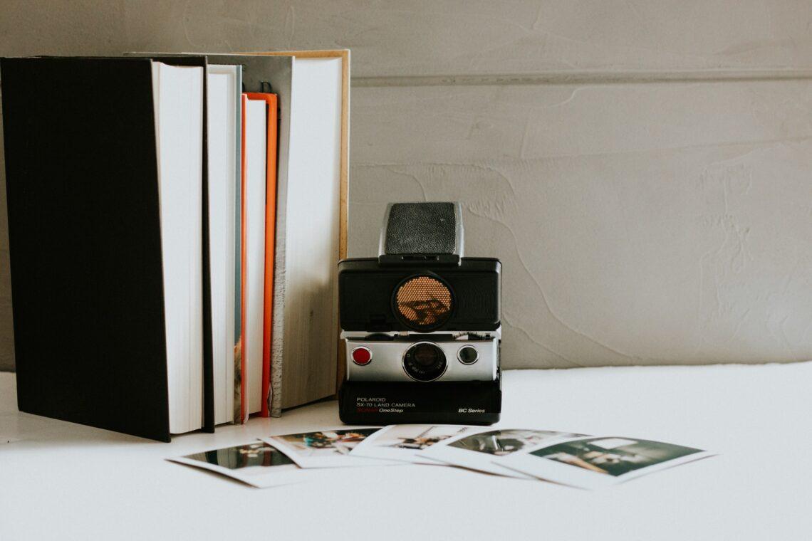 quattro libri disposti dal lato delle pagine, una polaroid e delle foto di cui non si distinguono bene i soggetti