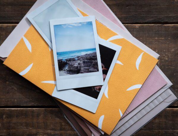 delle polaroid di paesaggi appoggiate su una pila di buste da lettera